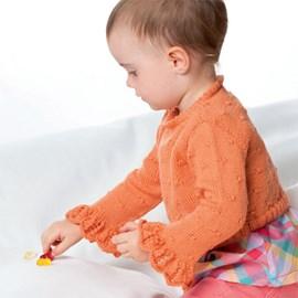 Gebreide trui met roezels aan de mouwen.