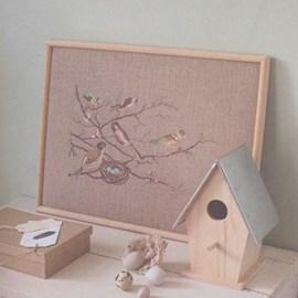 Borduurwerk van een tak met vogeltjes.