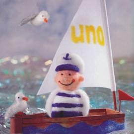 Vilten zeeman, boot en zeemeeuwen.
